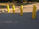 These plastic bollards are bolted in to the ground at Lakeline Station in Cedar Park, Texas. I'm not sure if they're to correct a mistake or block off traffic for a future larger intersection outside.